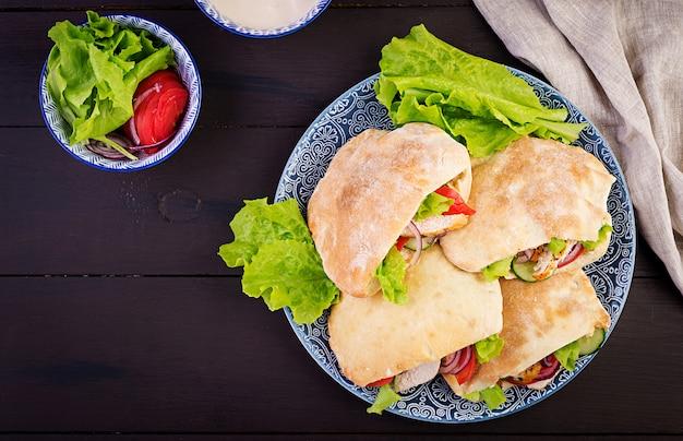 Pão árabe recheado com frango, tomate e alface na mesa de madeira. cozinha do oriente médio. vista do topo