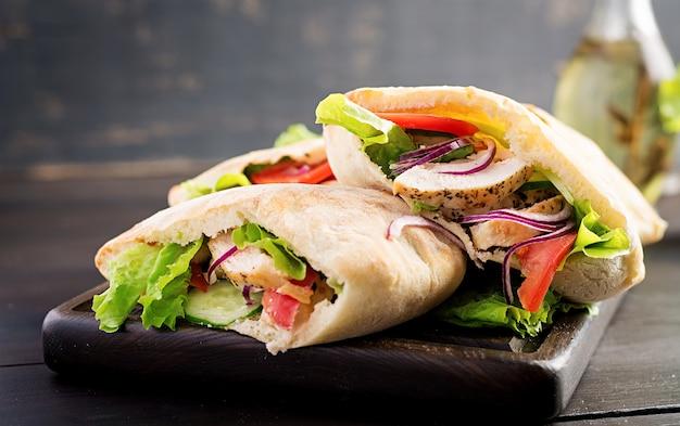 Pão árabe recheado com frango, tomate e alface na mesa de madeira. cozinha do oriente médio.