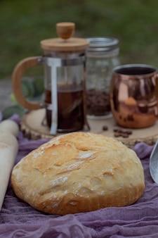 Pão artesanal na toalha de mesa acompanhado de conjunto de café