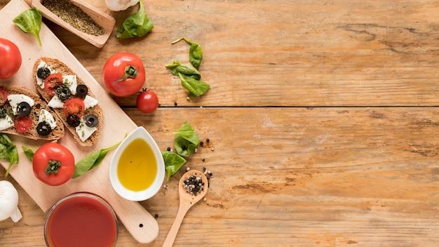Pão assado com cobertura e legumes na tábua de cortar