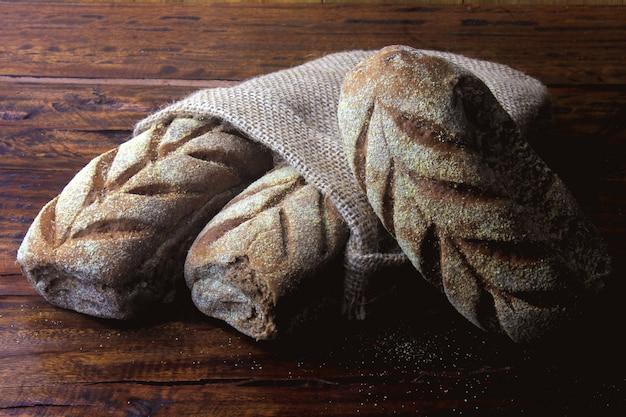 Pão australiano dentro de saco rústico sobre fundo de madeira rústico