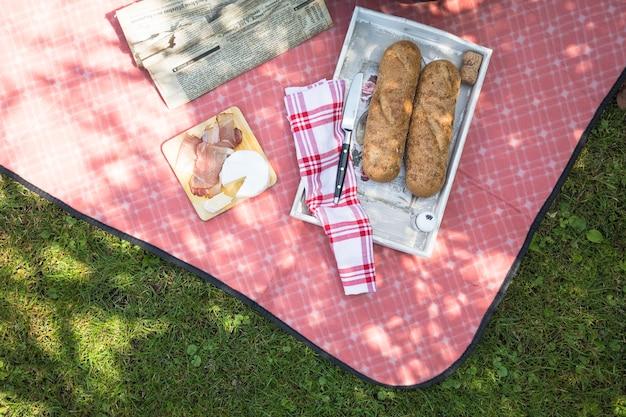 Pão; bacon e queijo na toalha de mesa vermelha na grama verde