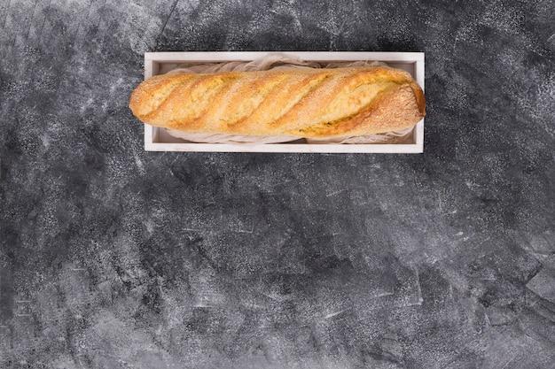 Pão baguete na caixa de madeira no pano de fundo texturizado preto