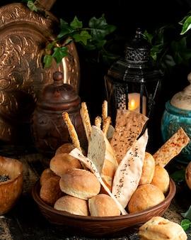 Pão baguete palitos e pães com gergelim na tigela