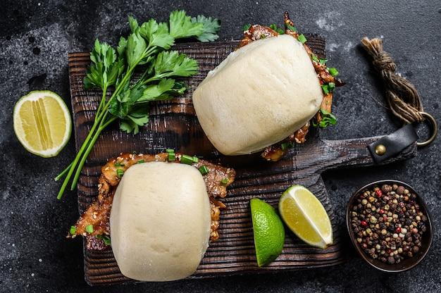 Pão bao cozido no vapor com barriga de porco e legumes. fundo preto. vista do topo. Foto Premium