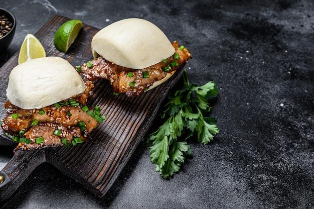 Pão bao cozido no vapor com barriga de porco e legumes. fundo preto.
