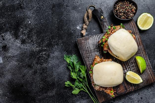 Pão bao cozido no vapor com barriga de porco e legumes.