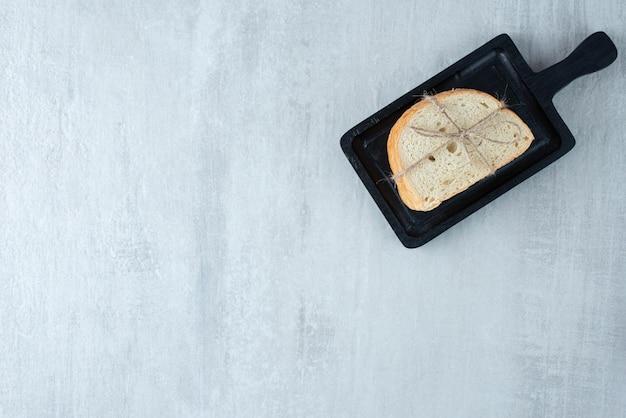 Pão branco amarrado com corda no quadro escuro.