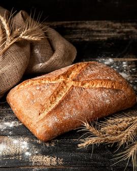 Pão branco com farinha crocante e trigo na mesa