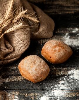 Pão branco com farinha e trigo na mesa