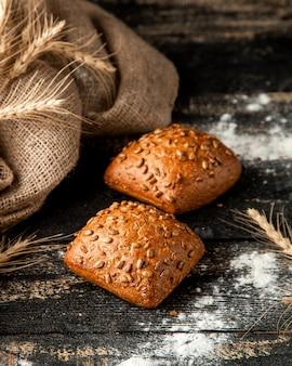 Pão branco com sementes de abóbora trigo e farinha na mesa