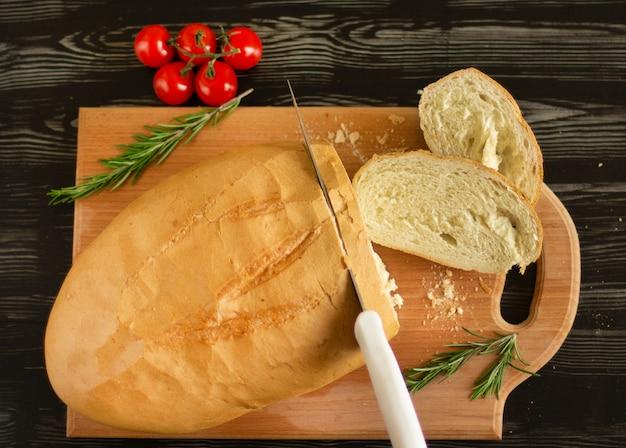 Pão branco é cortado com uma faca em uma placa de madeira com tomate cereja e alecrim