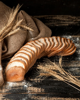 Pão branco em fatias de pão branco com trigo e farinha na mesa