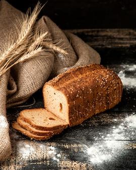 Pão branco fatiado de pão com sementes de trigo e farinha na mesa