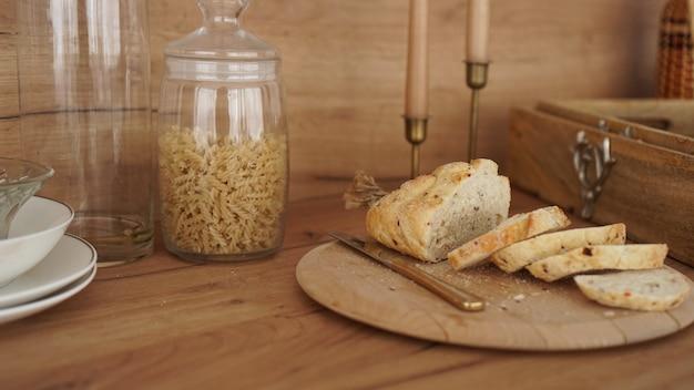 Pão branco fatiado em uma bandeja de madeira. cozinha moderna de estilo escandinavo. macarrão em uma jarra de vidro
