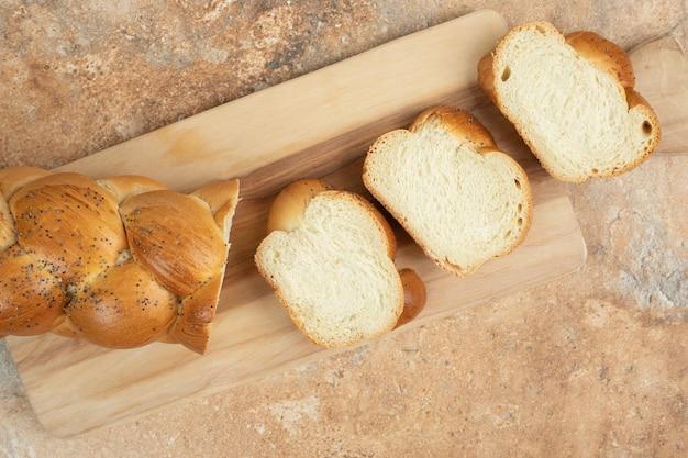 Pão branco fresco fatiado na tábua de madeira.
