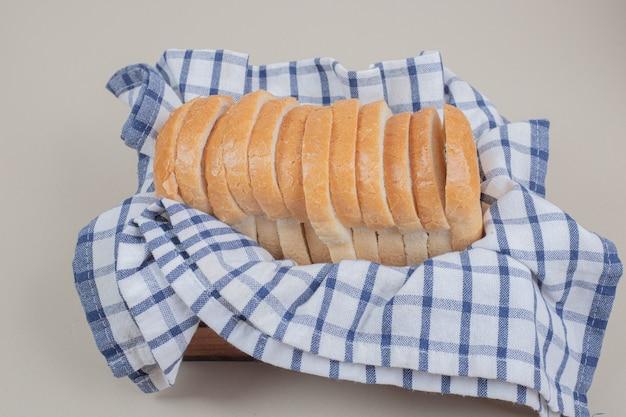 Pão branco fresco fatiado na toalha de mesa
