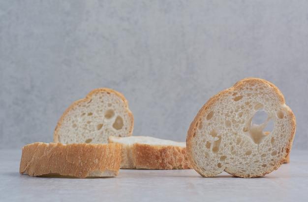 Pão branco fresco redondo sobre fundo de mármore.