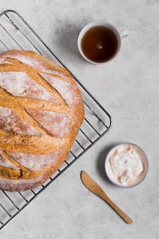 Pão branco redondo na bandeja e xícara de chá