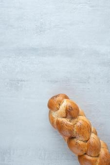 Pão branco trançado na mesa de pedra.