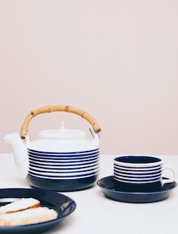 Pão; bule e xícara de café na mesa contra o fundo colorido