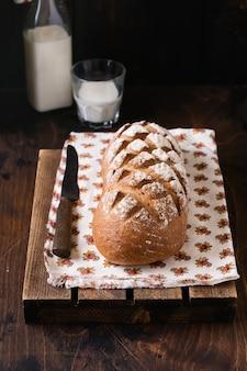Pão caseiro acabado de cozer com leite em uma velha mesa de madeira. estilo rústico