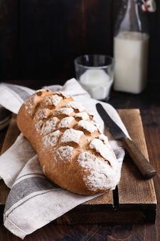 Pão caseiro acabado de cozer com leite em uma velha mesa de madeira. estilo rústico.