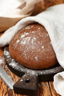 Pão caseiro acabado de cozer, farinha e uma faca sobre uma velha mesa de madeira