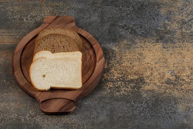 Pão caseiro branco e preto em tábua de madeira
