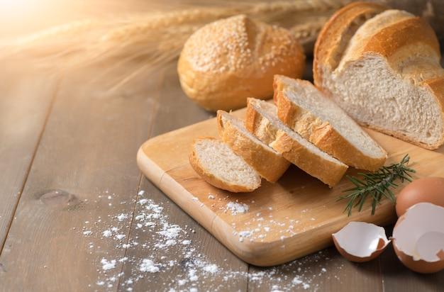 Pão caseiro cortado no bloco de madeira e no fundo de madeira, conceito da padaria