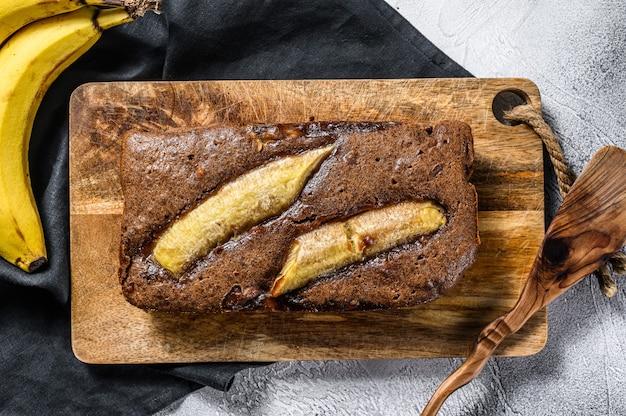 Pão caseiro de banana de chocolate com noz. plano de fundo cinza. vista do topo.