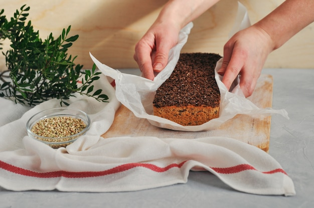 Pão caseiro do vegetariano em um fermento do trigo mourisco verde com sementes de linho, girassol nas mãos das mulheres em um fundo de madeira. nutrição saudável e adequada.