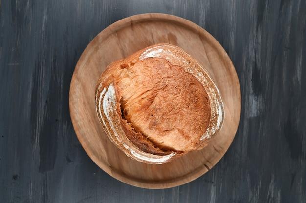 Pão caseiro em madeira escura. foto de alta qualidade