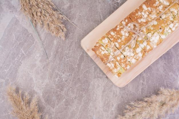 Pão caseiro em uma bandeja de madeira com plantas de trigo ao redor.