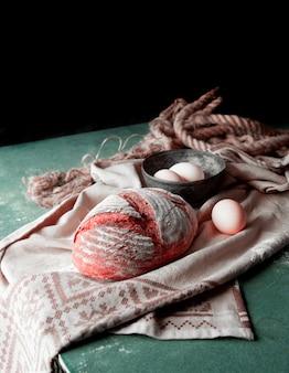 Pão caseiro em uma toalha branca com farinhas na parte superior com tigela de ovo ao redor.