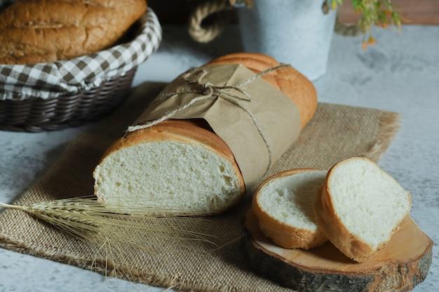 Pão caseiro fresco amarrado com corda na superfície da pedra.
