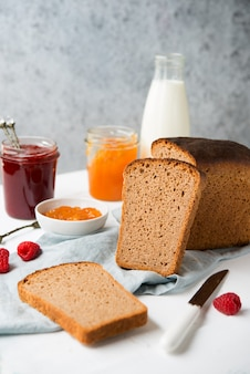 Pão caseiro fresco com geléia e leite, comida caseira simples, fundo claro