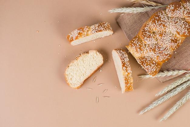 Pão caseiro fresco com sementes de gergelim na padaria, um conceito moderno na parede bege pastel, vista superior, copie o espaço