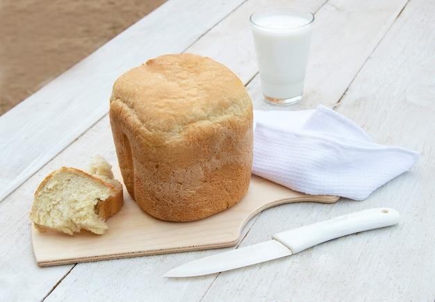 Pão caseiro fresco e um copo de iogurte orgânico caseiro natural em um fundo branco de madeira