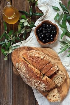 Pão caseiro fresco na placa de corte de madeira, no azeite, nas azeitonas e nas folhas da oliveira.