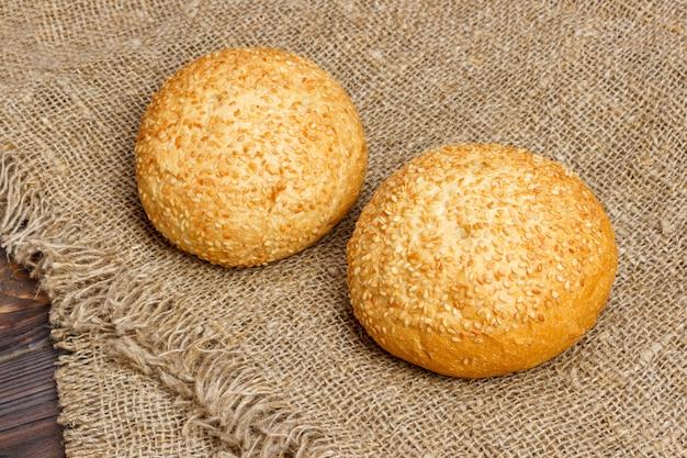 Pão caseiro fresco rolos com sementes de gergelim na mesa de madeira