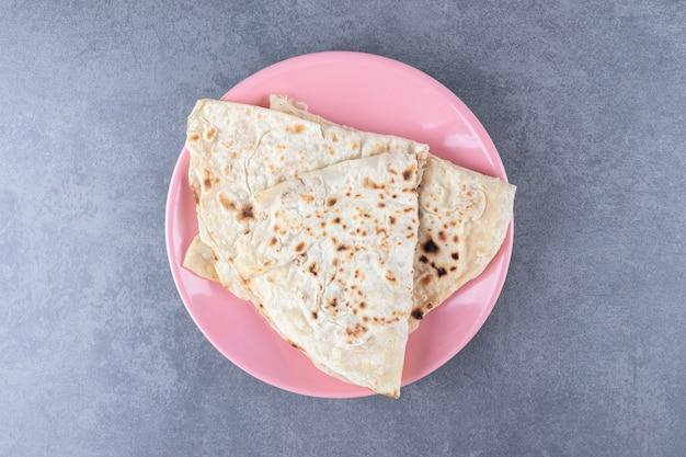 Pão caseiro lavash num prato, no mármore.