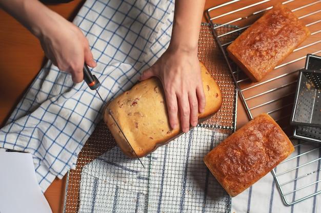 Pão caseiro na mesa da cozinha com corte de mão de mulher