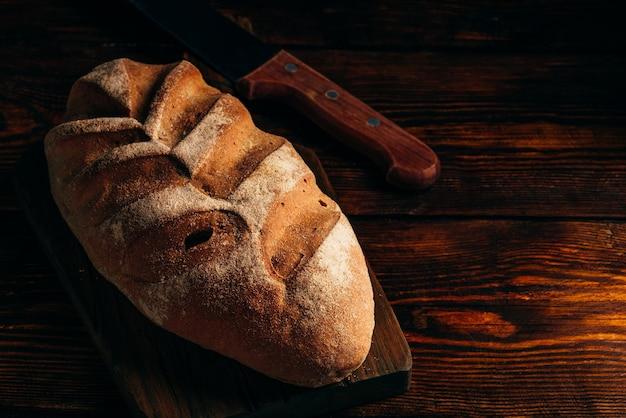 Pão caseiro na tábua com faca sobre fundo escuro de madeira.