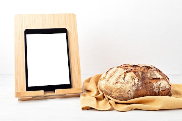 Pão caseiro orgânico fresco e bloco de notas com espaço de cópia. alimentação saudável, aplicação de culinária, conceito de receitas de pão online.