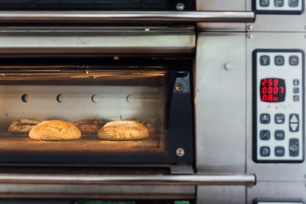 Pão caseiro que coze no forno elétrico. forno de produção na padaria. assando pão.