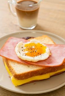 Pão caseiro queijo torrado com cobertura de presunto e ovo frito com linguiça de porco e café no café da manhã