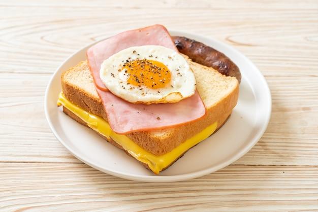 Pão caseiro queijo torrado com presunto e ovo frito com linguiça de porco no café da manhã