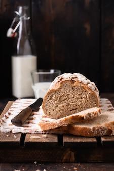 Pão caseiro recém-assado com leite em uma velha mesa de madeira