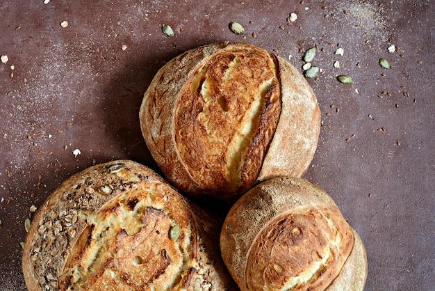 Pão caseiro recém-assado feito de trigo e farinha integral em fundo marrom.